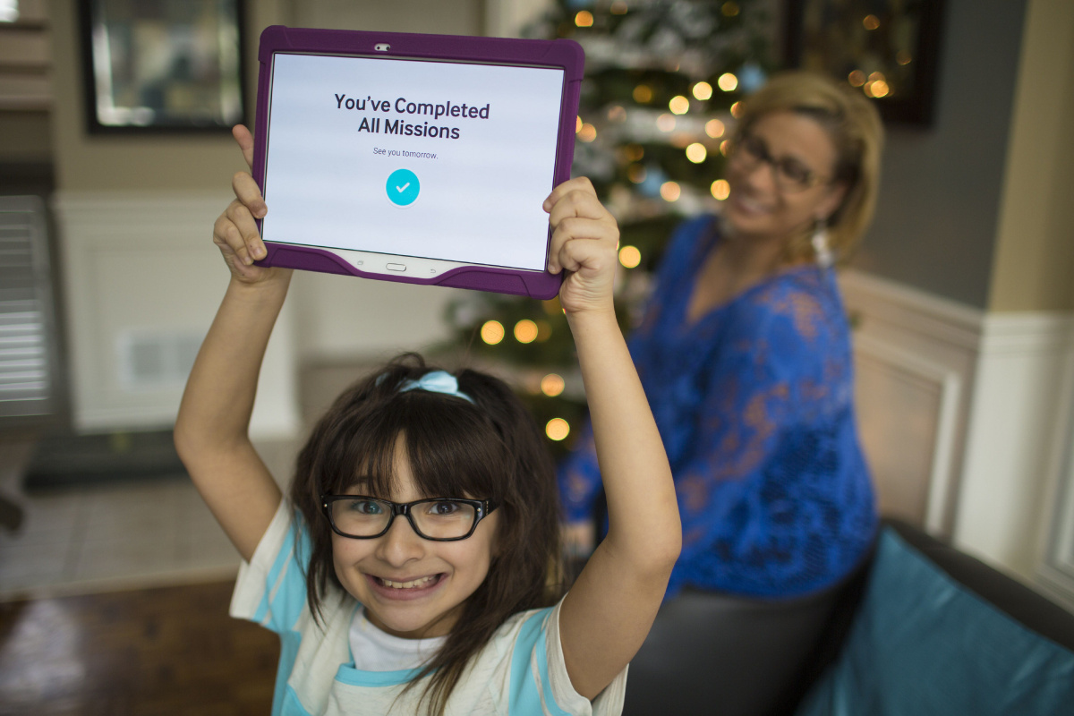 TORONTO, ON - DECEMBER 30  -  Emma Rose holds up her Samsung Galaxy tablet after completing her missions on the Look at Me app from Samsung while her mother Fi Ferraro looks on in the background.  December 30, 2014.  Samsung has launched a new app designed to help kids dealing with autism. To celebrate, they're giving away 200 tablets with the software to Canadian families with autistic kids. Carlos Osorio/Toronto Star